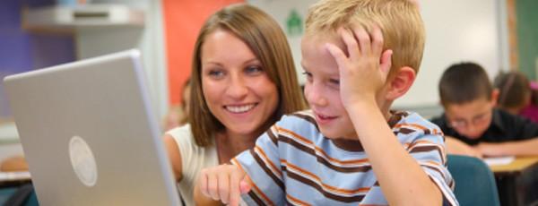 Lehrerin und kleiner Junge mit Notebook