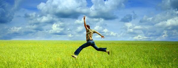 Junger Mann springt auf einer Wiese